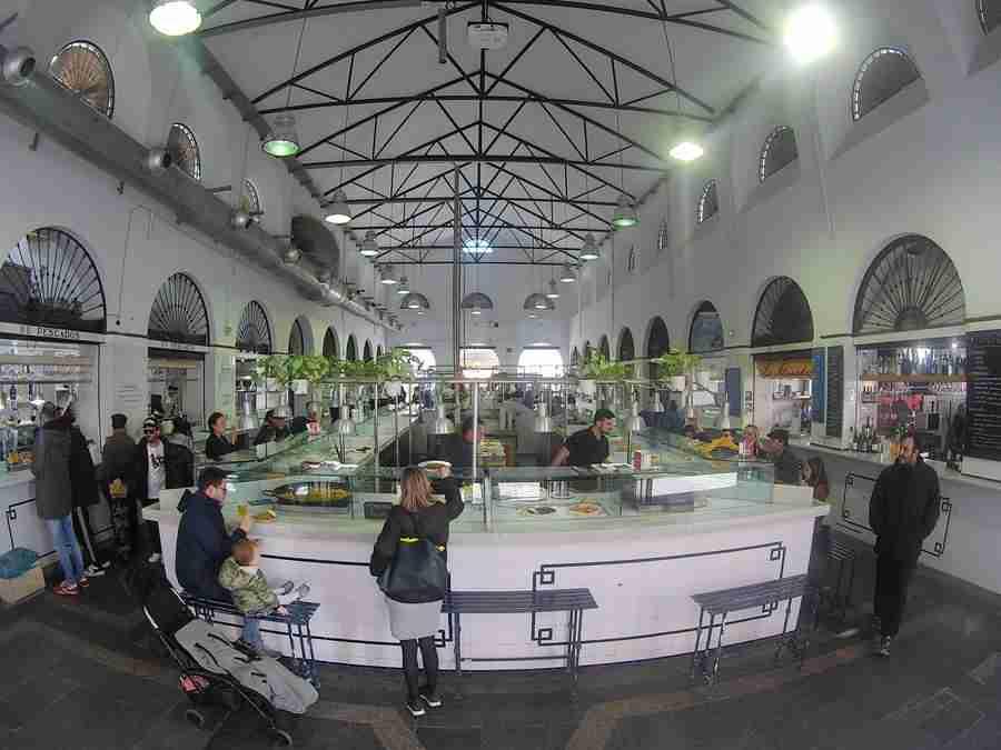 Vemos la galería de un mercado, con gente sentada comiendo en la barra y comprando alimentos a un lado.