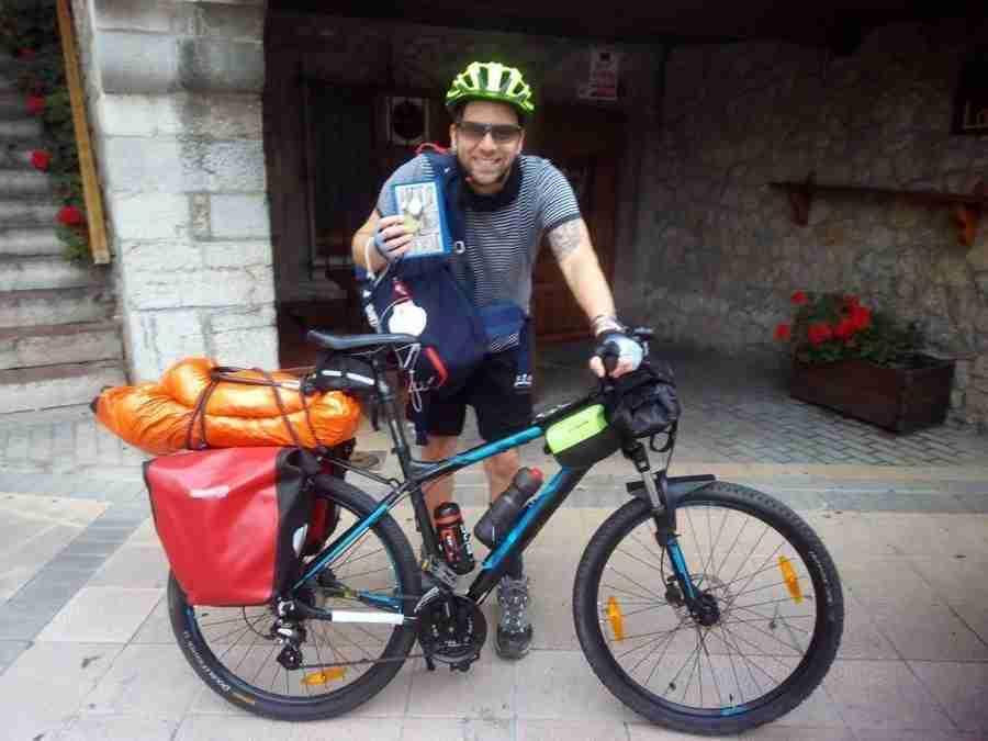 Vemos un hombre joven con su bicicleta, listo para salir de viaje.