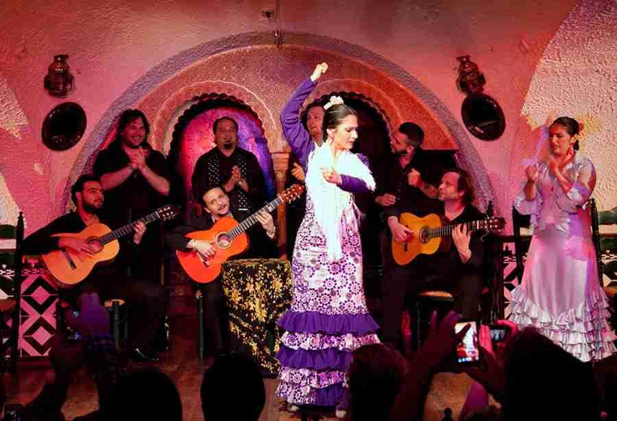 Imagen de un tablao flamenco, con bailaora y músicos.
