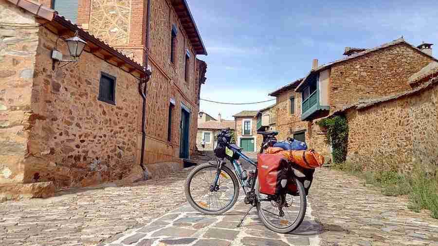 Vemos una bicicleta equipada para viajes sobre una callejuela de un pueblo.