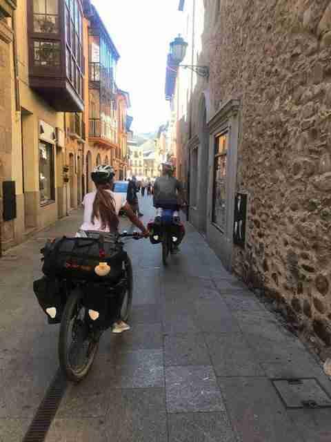 Vemos dos jóvenes viajando en bicicleta, con equipajes, por las callejuelas de una ciudad antigua.