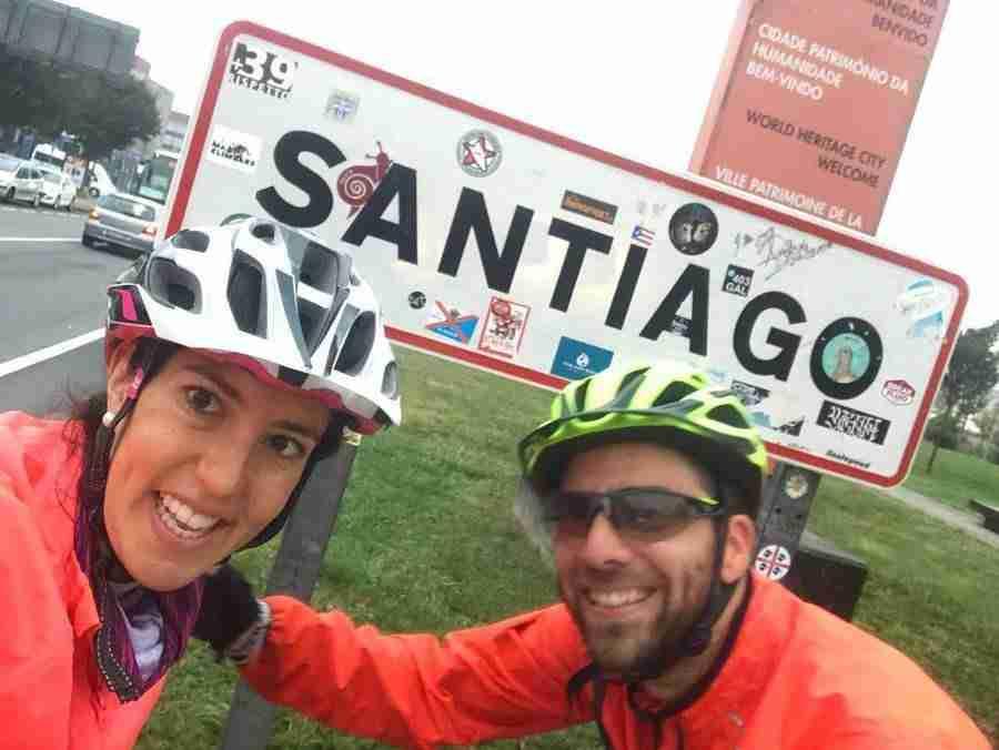 """Dos jóvenes adultos posan en frente de un cartel de la carretera que pone """"Santiago"""""""