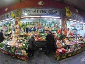 Vemos un puesto de mercado, con frutas y vegetales.
