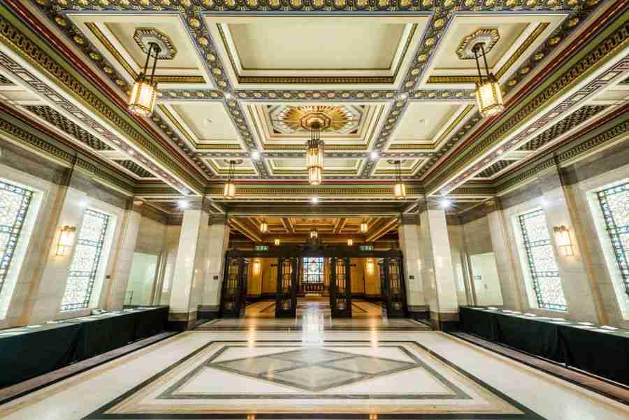 Un hall de entrada de un edificio art decó, iluminado por lámparas y ventanas. Muy opulento.