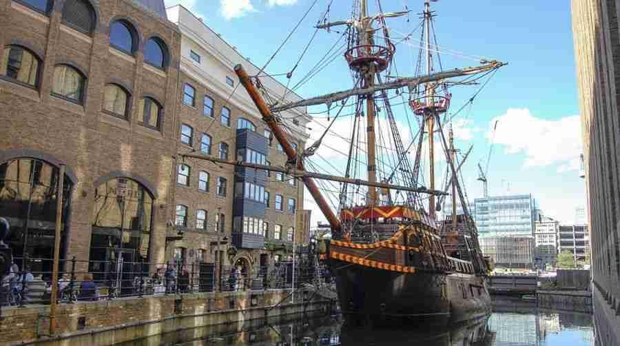 Un barco de vela de estilo antiguo, anclado en un muelle de la ciudad