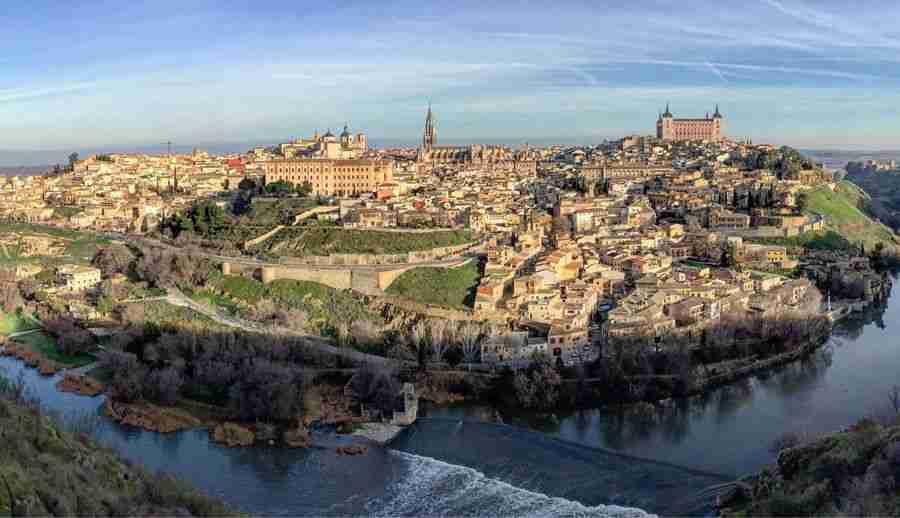 vista de una ciudad medieval con un río en el primer plano.