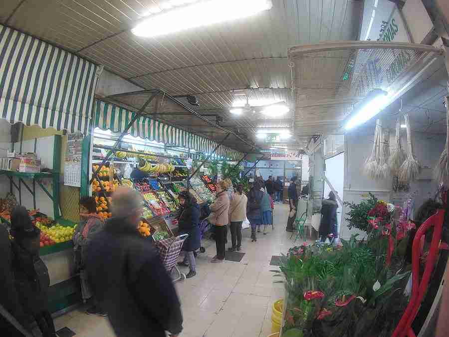 """Vemos un pasillo del mercado """"Las Palmeritas"""" de Sevilla, con plantas y vegetales en oferta."""