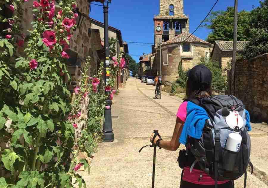 Muchacha haciendo una peregrinación a pie por un pueblo.