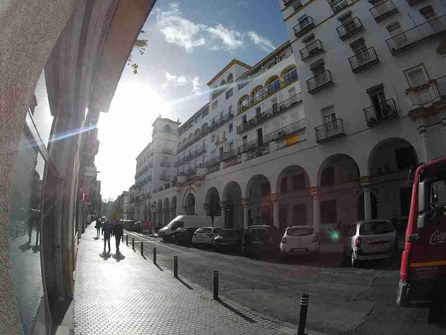 Vemos la fachada principal del mercado del Arenal, en Sevilla, un edificio blanco, grande y con arcadas.