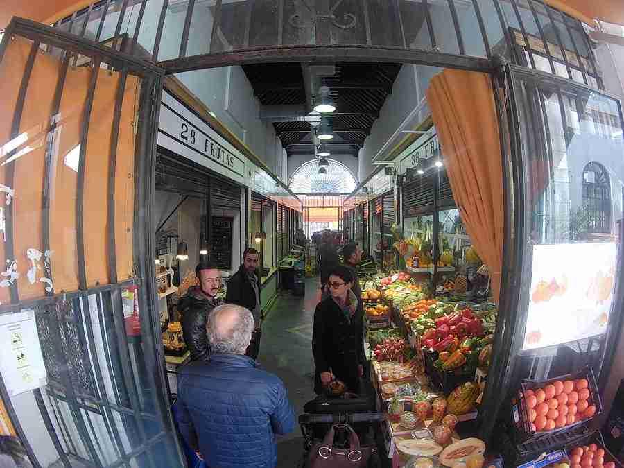 Vemos los pasillos de un mercado en Sevilla, con frutas y verduras exhibidas en un stand y gente comprando.