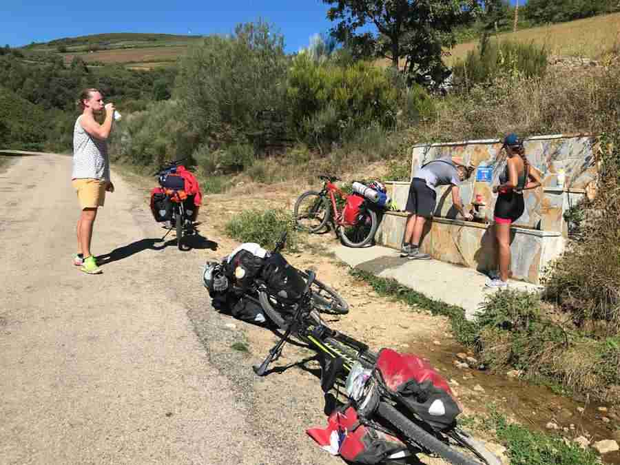 Vemos un grupo de adultos jóvenes en bicicletas, haciendo una parada para refrecarse.