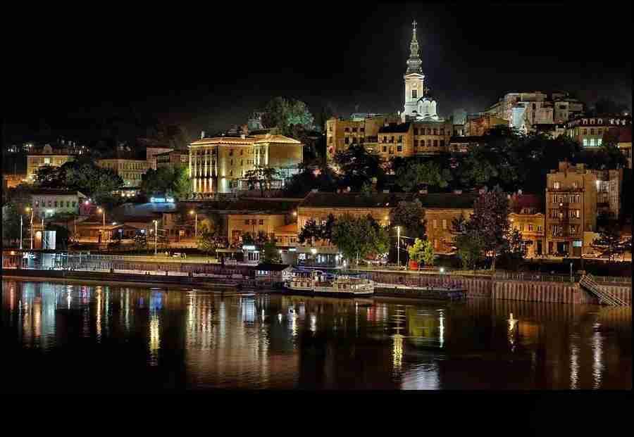 Vemos la ciudad de Belgrado sobre el rio Danubio, a la noche, con una iglesia de fondo.