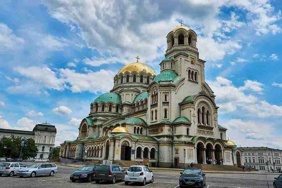 Vemos una catedral muy grande, en Sofía, Bulgaria, de estilo cristiano ortodoxo, con cúpulas redondas, y paredes blancas. Sofia es una de las 10 Ciudades baratas para visitar en Europa en 2019.
