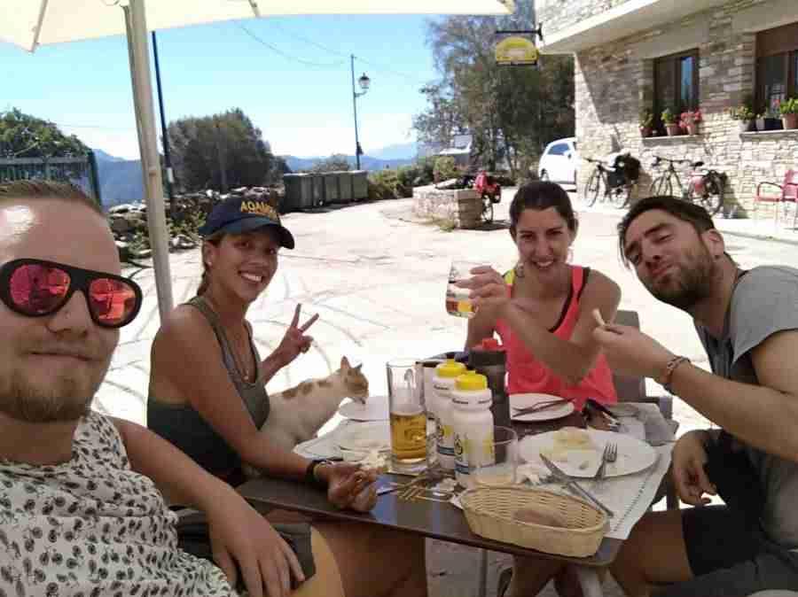Vemos un grupo de adultos jóvenes tomando un refrigerio en una terraza, al sol, parece verano.