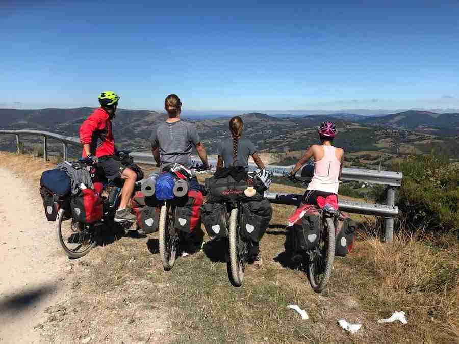 Vemos 4 adultos jóvenes en bicicletas contemplando el paisaje.