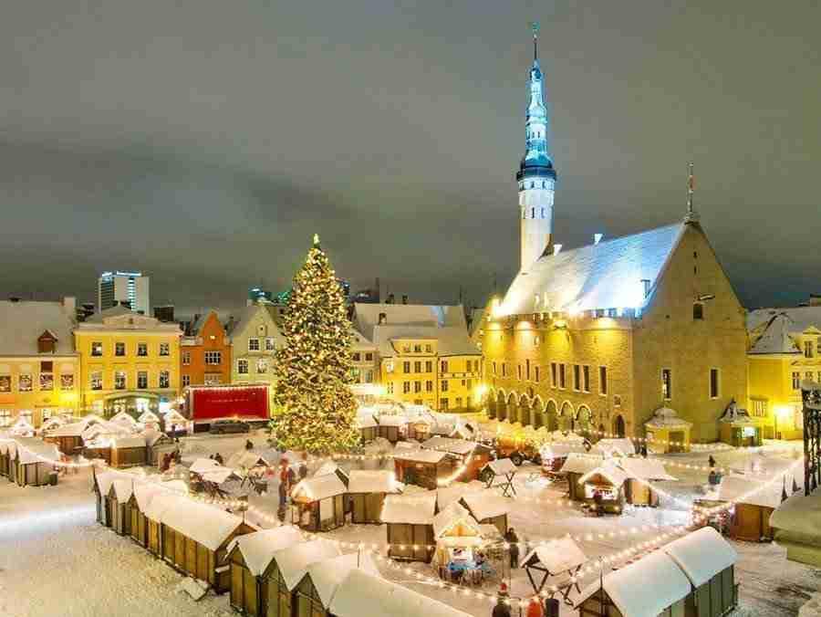 Vista parcial de la ciudad de Tallin en Estonia, vemos una plaza cubierta de nieve, con una iglesia al fondo y un arbol de navidad.